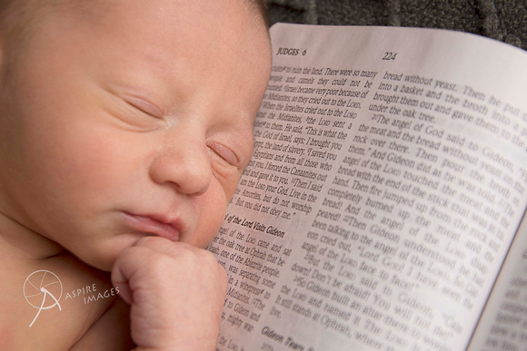 Newborn baby laying on Bible with name verse.