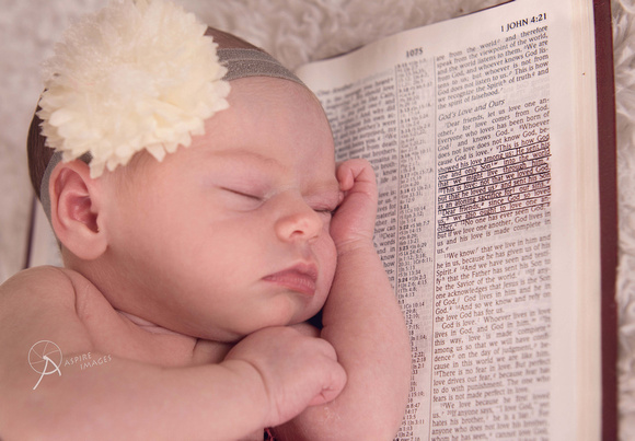 Newborn baby girl laying on Bible with name verse.
